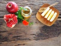 Manzanas, granadas y miel en el tablero de madera con la comida del concepto seleccionada en el hashanah judío del rosh del día d imagen de archivo