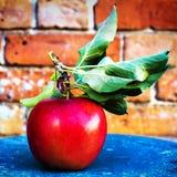 Manzanas grandes rojas con las hojas verdes en el fondo rústico del vintage, c Imagen de archivo libre de regalías