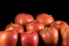 Manzanas jugosas con las gotitas de agua en fondo negro fotos de archivo