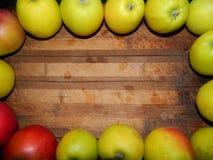 Manzanas jugosas grandes enmarcadas por un tablero de madera ancho Imágenes de archivo libres de regalías