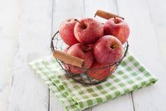 Manzanas jugosas rojas frescas en una cesta en una materia textil verde en un fondo de madera Imágenes de archivo libres de regalías