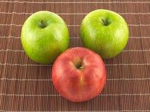 Manzanas maduras en cierre de mimbre marrón de la estera de la paja para arriba Imagen de archivo