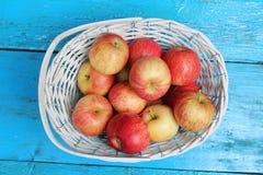 Manzanas maduras en la cesta de mimbre blanca Imagen de archivo