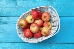 Manzanas maduras en la cesta de mimbre blanca Imagenes de archivo