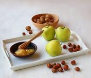 Manzanas, miel y nueces en una bandeja blanca Foto de archivo