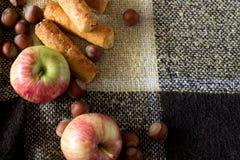 Manzanas, nueces, galletas en el fondo Fotografía de archivo libre de regalías