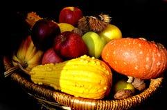 Manzanas, nueces y calabaza coloridas en una cesta de madera aislada en el fondo negro - vida de la calma del otoño fotos de archivo
