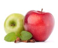 Manzanas, palillos de canela y de menta todavía de las hojas vida rojos y verdes Fotos de archivo