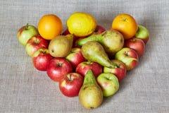 Manzanas, pera, naranja y limón en una lona gris Fotografía de archivo
