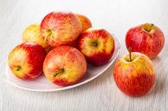 Manzanas rayadas rojas en plato, dos manzanas en la tabla de madera imágenes de archivo libres de regalías