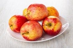 Manzanas rayadas rojas en plato en la tabla de madera fotos de archivo