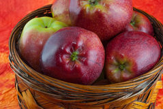 Manzanas red delicious en cesta de mimbre en fondo amarillo y anaranjado Foto de archivo libre de regalías