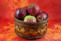 Manzanas red delicious en cesta de mimbre en fondo amarillo y anaranjado Imagen de archivo libre de regalías