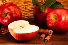 Manzanas rojas con los palillos de cinamomo Imágenes de archivo libres de regalías