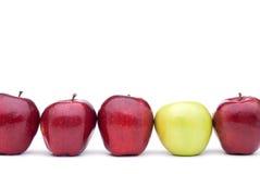 Manzanas rojas con una manzana verde Fotografía de archivo libre de regalías