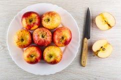 Manzanas rojas de la raya en el plato blanco, cuchillo, mitades de la manzana en la tabla de madera Visi?n superior foto de archivo