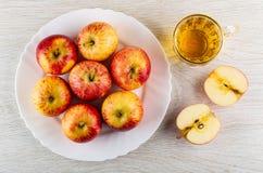 Manzanas rojas de la raya en el plato blanco, taza del zumo de manzana, mitades de la manzana en la tabla Visi?n superior fotos de archivo