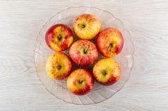 Manzanas rojas de la raya en plato transparente en la tabla de madera Visi?n superior imágenes de archivo libres de regalías