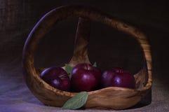 Manzanas rojas en cesta de madera con pocas hojas verdes en saco natural Imagenes de archivo
