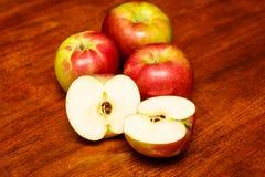 Manzanas rojas en la tabla de madera con una partida en dos Imagen de archivo libre de regalías