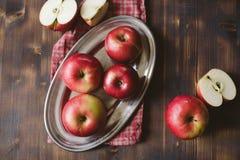 Manzanas rojas en la tabla de madera del tablón Fotos de archivo
