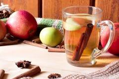 Manzanas rojas en un tablero de madera, una taza de cristal de herbario o un té y un canela Foto de archivo libre de regalías