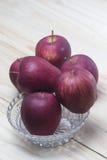 Manzanas rojas en un vector de madera Imagenes de archivo