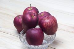 Manzanas rojas en un vector de madera Foto de archivo libre de regalías