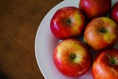 Manzanas rojas en una placa blanca Imagen de archivo libre de regalías