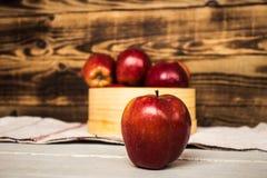 Manzanas rojas encendido en cuenco de madera Foto de archivo libre de regalías