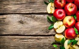 Manzanas rojas frescas con las hojas verdes en la tabla de madera Imagen de archivo