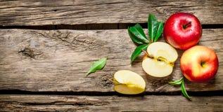 Manzanas rojas frescas con las hojas verdes en la tabla de madera Foto de archivo libre de regalías