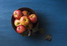 Manzanas rojas frescas del otoño en un cuenco de cerámica en un fondo azul, visión superior Imagen de archivo libre de regalías