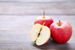 Manzanas rojas frescas en un fondo de madera gris foto de archivo libre de regalías