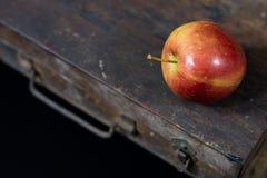 Manzanas rojas grandes en una caja de madera oscura Cajón de madera y manzanas encendido Fotografía de archivo libre de regalías