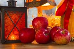 Manzanas rojas, linterna anaranjada, una botella del aceite de girasol, oídos de w Foto de archivo libre de regalías