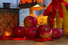 Manzanas rojas, linterna anaranjada, una botella del aceite de girasol, oídos de w Imagenes de archivo