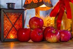 Manzanas rojas, linterna anaranjada, una botella del aceite de girasol, oídos de w Imagen de archivo libre de regalías