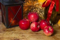 Manzanas rojas, linterna anaranjada, una botella del aceite de girasol, oídos de w Fotos de archivo libres de regalías