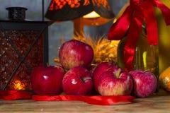 Manzanas rojas, linterna anaranjada, una botella del aceite de girasol, oídos de w Fotos de archivo