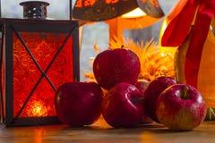 Manzanas rojas, linterna anaranjada, una botella del aceite de girasol, oídos de w Imágenes de archivo libres de regalías