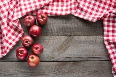 Manzanas rojas maduras a bordo con la servilleta a cuadros roja alrededor y el espacio de la copia Fotografía de archivo
