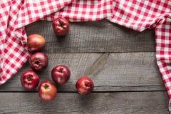 Manzanas rojas maduras a bordo con la servilleta a cuadros roja alrededor y el espacio de la copia Imágenes de archivo libres de regalías
