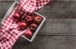 Manzanas rojas maduras en abedul-caja en el tablero de madera con la servilleta a cuadros roja alrededor y el espacio de la copia Imágenes de archivo libres de regalías