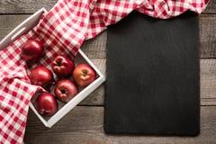 Manzanas rojas maduras en abedul-caja en el tablero de madera con la servilleta a cuadros roja alrededor y espacio de la copia en Fotografía de archivo libre de regalías