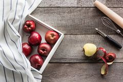 Manzanas rojas maduras en bandeja del abedul blanco con la servilleta en el tablero de madera, los accesorios para cocer y el esp Imagenes de archivo