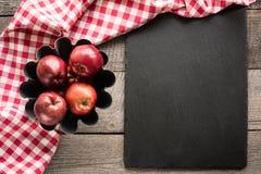 Manzanas rojas maduras en el tablero de madera con la toalla a cuadros roja alrededor y los accesorios para cocer Foto de archivo libre de regalías