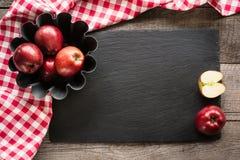 Manzanas rojas maduras en el tablero de madera con la toalla a cuadros roja alrededor y los accesorios para cocer Visión superior Fotos de archivo libres de regalías