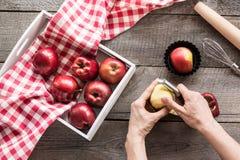 Manzanas rojas maduras en una caja del abedul en un tablero de madera Manzanas de la cáscara de la mujer para cocinar un cuchillo Fotografía de archivo