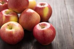Manzanas rojas maduras frescas en fondo de madera Fotos de archivo